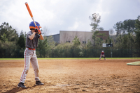 Side view of boy swinging baseball bat on field