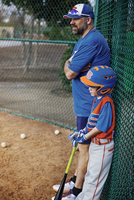 Side view of thoughtful baseball player and coach standing by chainlink fence on field