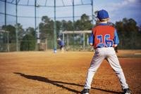 Rear view of boy playing baseball on field