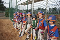 Baseball team standing by chainlink fence on field