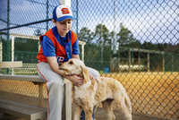 Baseball player stroking dog on field