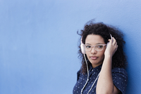 Thoughtful young woman listening music against blue background