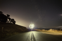 Person making heart shape while performing light painting on mountain road at night