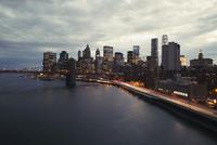 Brooklyn Bridge and illuminated city skyline at dusk