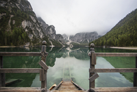 Wooden bridge by lake and mountains