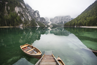 Boat moored on calm lake by mountains