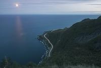 High angle view of long exposure on mountain road by sea at night