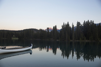 Reflection of trees and boat in calm lake during sunset