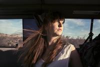 Thoughtful woman sitting in car during vacation 11100039622| 写真素材・ストックフォト・画像・イラスト素材|アマナイメージズ