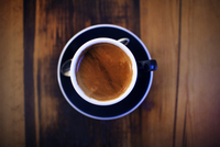 Overhead view of coffee cup on wooden table