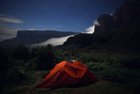 Tent on green mountain at dusk