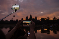 Cropped image of tourists photographing silhouette Angkor Wat temple during sunset