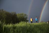 Friends running on grassy field against sky with double rainbow 11100039982  写真素材・ストックフォト・画像・イラスト素材 アマナイメージズ