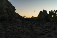 Low angle view of silhouette person zip-lining over mountains against clear sky