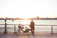 Rear view of senior woman standing by Citi Bike against sea during sunset