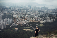 High angle view of man looking at cityscape while standing on rock