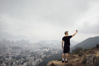 Man taking selfie while standing on rock by cityscape during foggy weather