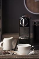 Coffee cup and jar with machine on wooden table