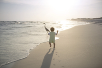 Rear view of boy running towards heron at beach during sunset 11100040179| 写真素材・ストックフォト・画像・イラスト素材|アマナイメージズ