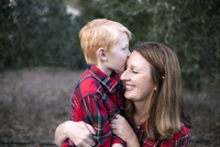 Boy kissing happy mother