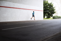 Rear view of male athlete running on sidewalk by road