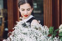 Female florist holding white flowers outside flower shop 11100040786| 写真素材・ストックフォト・画像・イラスト素材|アマナイメージズ