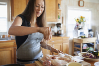 Woman seasoning chicken in kitchen