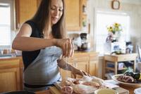 Woman seasoning chicken in kitchen 11100040875| 写真素材・ストックフォト・画像・イラスト素材|アマナイメージズ