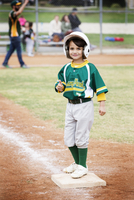 Portrait of smiling boy showing thumbs up on baseball field