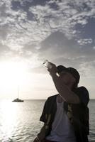 Young man drinking beer by sea