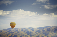Hot air balloon flying over mountains in Cappadocia