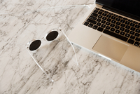 Overhead view of eyeglasses and laptop on marble table