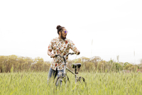 Man with bicycle on grassy field against clear sky