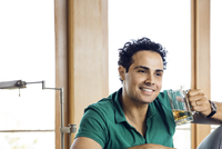 Happy man talking to male friend while holding beer glass at home