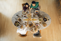 Overhead view of friends toasting drinks at dining table