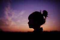 Silhouette girl against dramatic sky during sunset