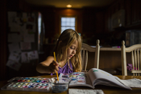 Girl drawing in book while sitting at table
