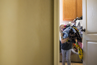 Girl carrying laundry clothes at home