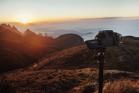 Video camera attached to tripod on mountain during sunset