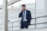 Confident businessman using smart phone at subway station 11100041910| 写真素材・ストックフォト・画像・イラスト素材|アマナイメージズ