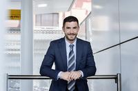 Portrait of confident businessman leaning on railing at subway station 11100041913| 写真素材・ストックフォト・画像・イラスト素材|アマナイメージズ