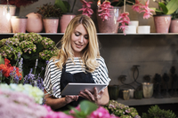 Florist using tablet computer in flower shop