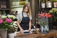 Owner using tablet computer in flower shop