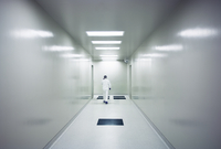 Rear view of scientist walking in corridor at hospital