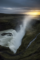 Scenic view of waterfall against cloudy sky during sunset