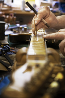 Cropped image of carpenter working on fretboard in workshop