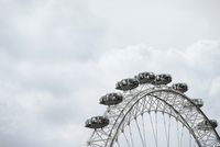 Low angle view of London Eye against cloudy sky