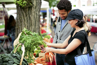 Multi-ethnic couple buying vegetables at market stall