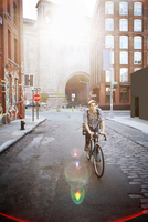 Man riding bicycle on street amidst buildings