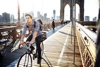 Man riding bicycle on Brooklyn Bridge against clear sky 11100042361| 写真素材・ストックフォト・画像・イラスト素材|アマナイメージズ